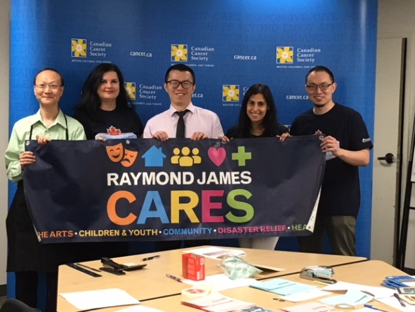 Raymond James care month banner held by group